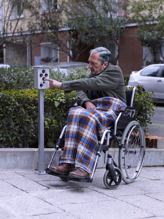 Wheelchair man pressing a button on a a remote control