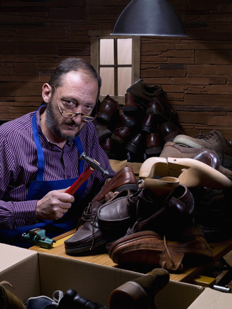 patrimony: Old man, shoemaker, repairing old shoe in his workshop