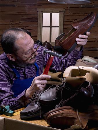 Old man, shoemaker, repairing old shoe in his workshop