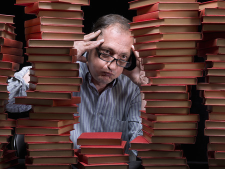 Man surrounded with books, in a library