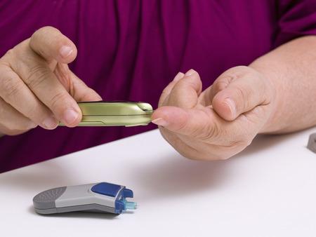 blood glucose level: Doing patient diabetes blood test glucose level using glucometer Stock Photo