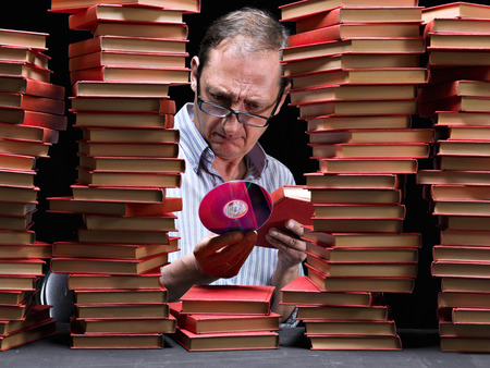 Man surrounded with books,examining a CD that has in the hand