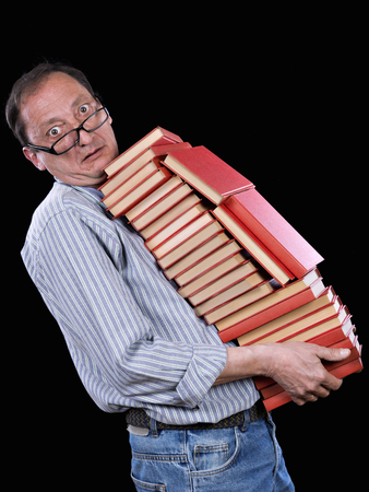 Mature man transporting a battery of books