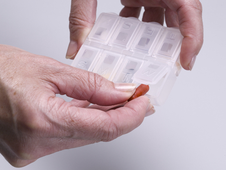 Close up of hands of an elderly woman taking a pill medicine