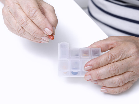 Close up of hands of an elderly woman taking a pill medicine Stok Fotoğraf - 36861703