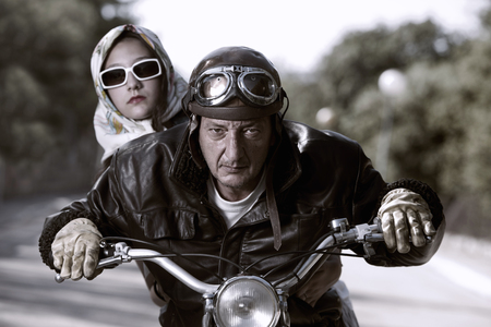 Old biker with helmet and goggles, accompanied by a woman Stok Fotoğraf