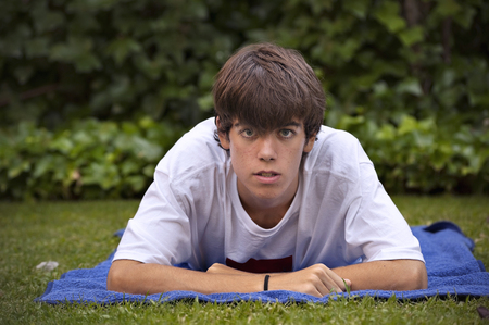Teenager, with acne knocked down in the grass Stok Fotoğraf