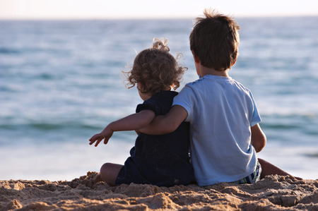 3 5 years: Two children sat in the sand, looking at the sea Stock Photo