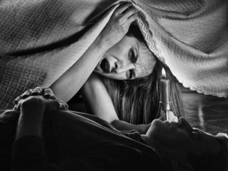 A girl with fear, looking under the bed and surprised because there is a corpse photo
