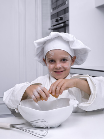 Children, dressed as a cook, breaking an egg