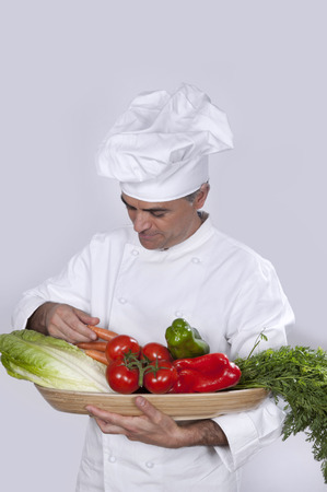 Chef with various vegetables in the hands