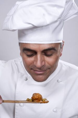 smelling: Chef smelling a spoonful of food