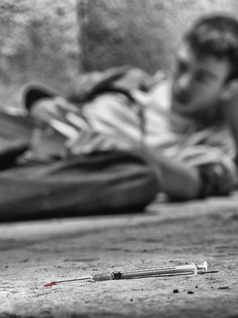 druggie: Young drug addict with a syringe in foreground Stock Photo