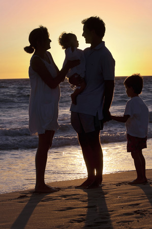 Family walking on the beach in sunset