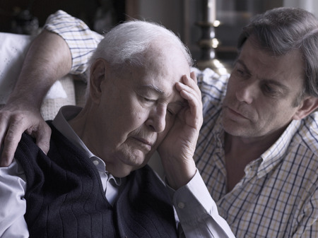 Portrait of an elderly man, comforted by his son Stockfoto