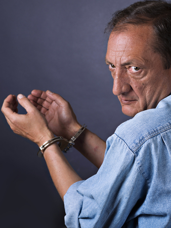 jailed: Man, mature, with handcuffs Stock Photo