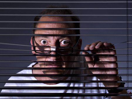 Vicious man looking sideways through venetian blind Stok Fotoğraf - 38156706