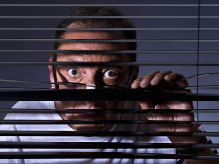 vicious: Vicious man looking sideways through venetian blind