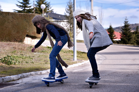Two girls playing with a wave board. Skateboard Stok Fotoğraf