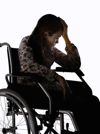 paraplegic: 12-a�os de edad, ni�a sentada en una silla de ruedas, en el fondo blanco Foto de archivo