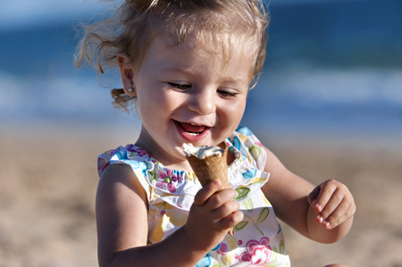 Small girl taking an ice cream in the beach Stok Fotoğraf