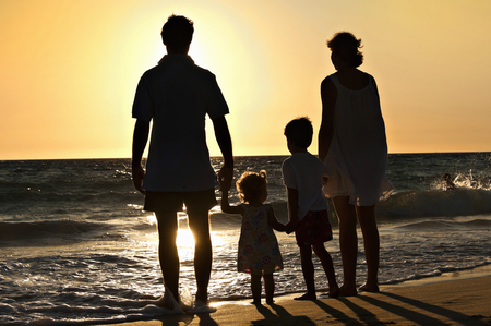 15 18: Family walking on the beach in sunset