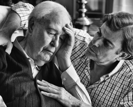 comforted: Portrait of an elderly man, comforted by his son Stock Photo