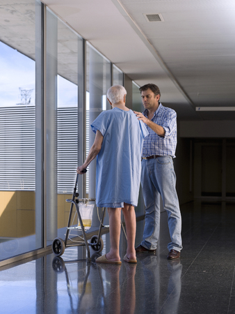 Elderly person in hospital, with the help of a walker