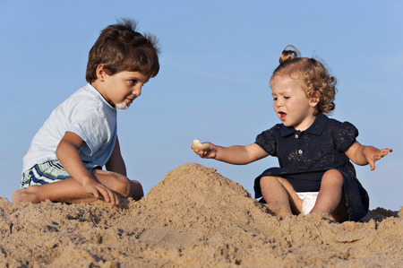 Two children have fun on the beach playing with the sand