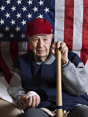 80 plus years: Old baseball player with bat and ball in front of an American flag