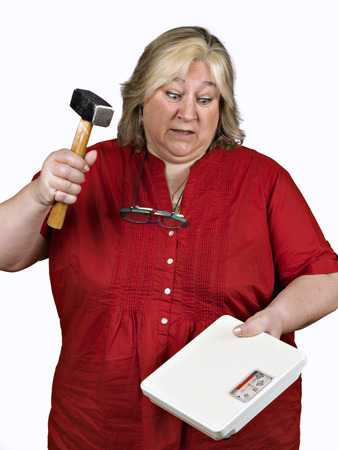 40 44 years: Woman furious, breaking a bathroom scale with a hammer