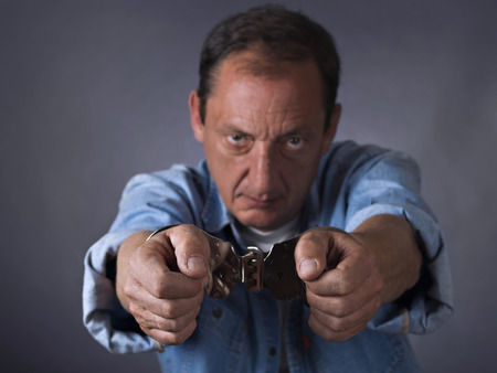 swindler: Man, mature, with handcuffs Stock Photo