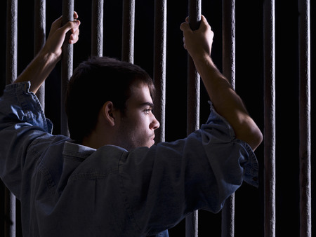 preso: Hombre encarcelado, mirando hacia abajo, se apoderó de algunos bares Foto de archivo