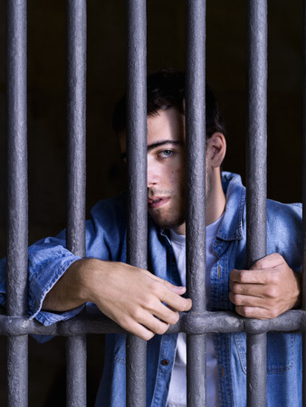 confined space: Imprisoned man, seized to a few bars Stock Photo