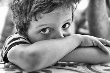 in tears: Niño, con los brazos cruzados, mirando a la cámara