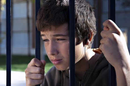 Young boy weeping behind a fence.