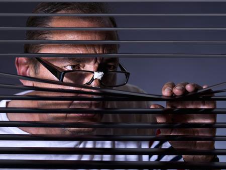 paranoia: Vicious man looking sideways through venetian blind
