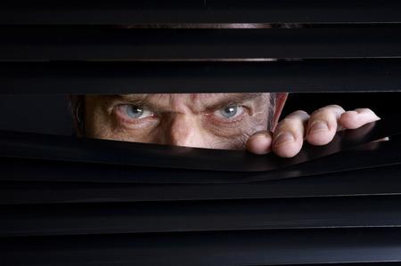 Hombre espiando algo a través de las persianas venecianas Foto de archivo - 38960114