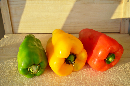 Three kinds of bell peppers - green, yellow and red - over a wood box illuminated by the sunset light Stock Photo