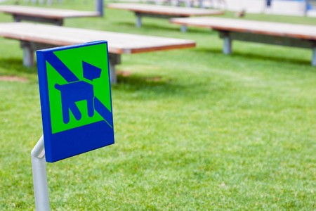 No dog sign in clear green park with picnic tables photo