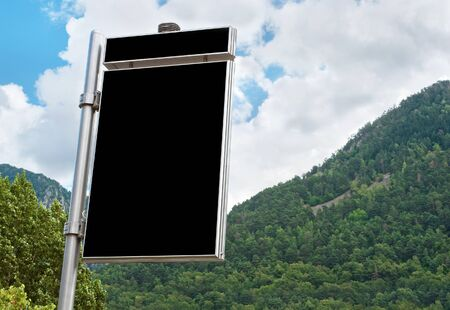 mountainous: Big empty billboard against beautiful mountainous landscape with green forest  Stock Photo