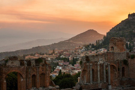 taormina: Taormina city during dramatic sunset, with the ancient greek amphitheatre, Sicily island, Italy
