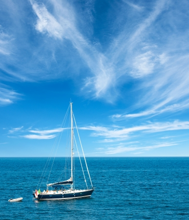 Luxury yatch in open waters with beautiful clouds Stock Photo