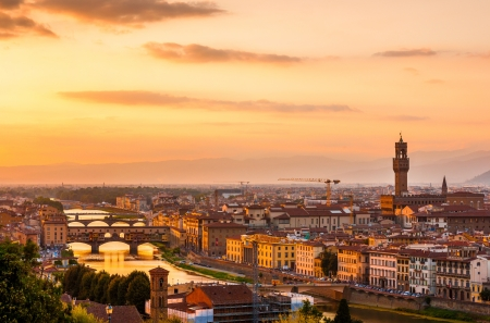 Golden sunset over the river Arno, with Ponte Vecchio and Palazzo Vecchio, Florence, Italy