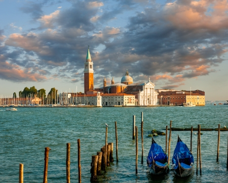 Dramatic sunset over San Gorgio island with gondolas in front, Venice, Italy