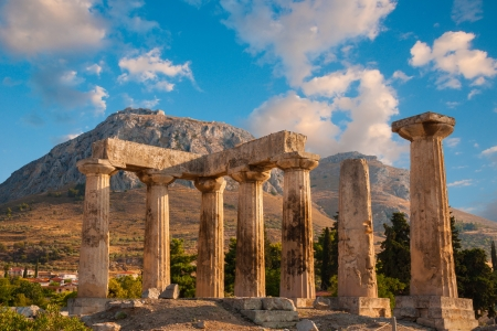 Ruins of Appollo temple with fortress at back in ancient Corinth, Greece photo
