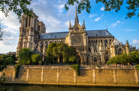 Gorgeous sunset over Notre Dame cathedral with puffy clouds, Paris, France