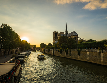 Sunset rays over Notre Dame cathedral with puffy clouds, Paris, France