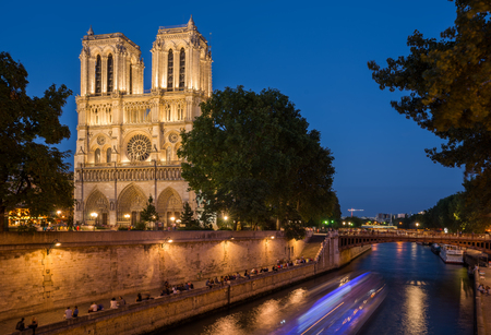 Notre Dame cathedral at dusk with blurred boat lights over Seine river, Paris, France