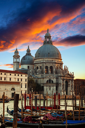 Dramatic sunset over Grand Canal and Basilica Santa Maria della Salute with gondolas in front, Venice, Italy